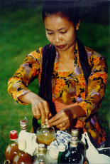 Indonesian woman preparing traditional medicine drink - jamu