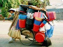 Typical seller of brooms and buckets travels the streets of Jakarta